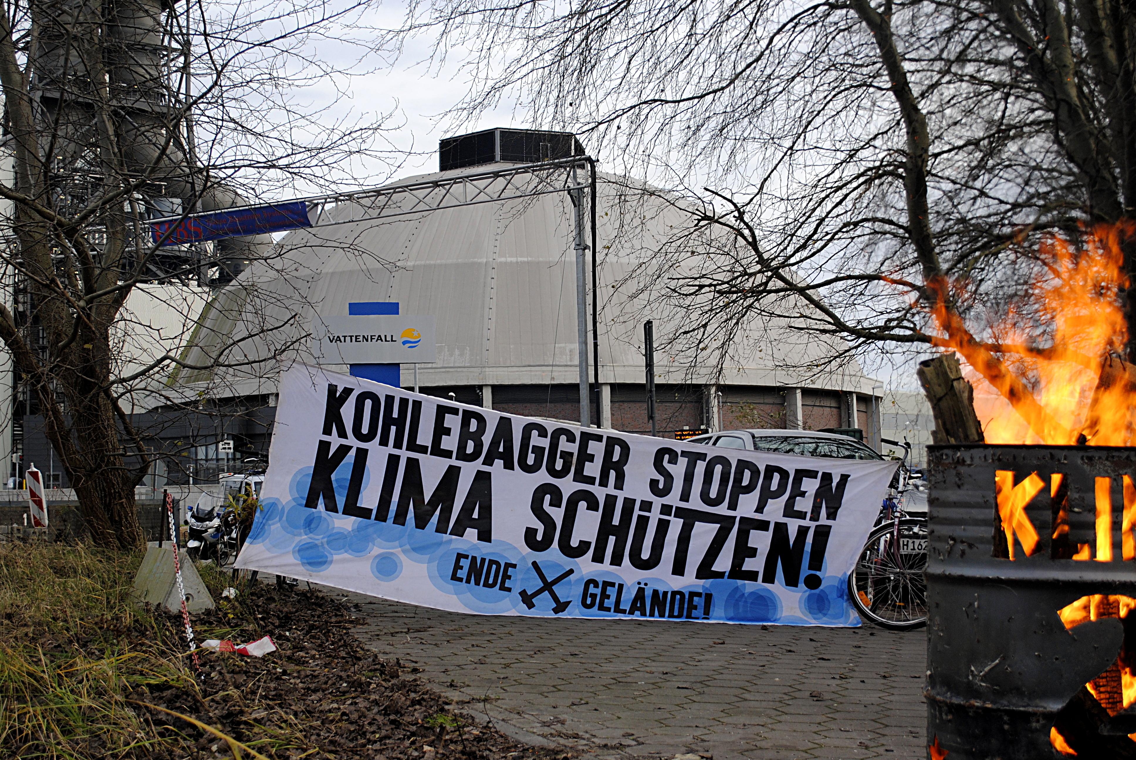 """Feuertonne mit Transparent im Hintergrund: """"Kohlebagger stoppen - Klima schützen! Ende Gelände"""""""